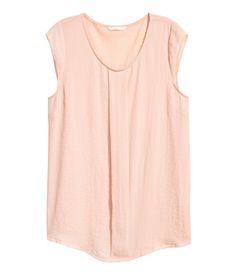 Powder pink. Top in woven crêped fabric with pleats at front, round neck, and cap sleeves. Back section in jersey.