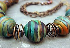Beautiful coloured beads and bronze wire spacers. Fiddlehead beads, polymer clay by Stories They Tell. Polymer Clay Kunst, Polymer Clay Necklace, Polymer Clay Pendant, Polymer Clay Projects, Polymer Clay Creations, Polymer Clay Earrings, Diy Fimo, Crea Fimo, Precious Metal Clay