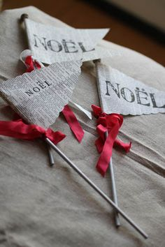 Book page pennant flags, stamped with Christmas sentiments, tied off with vintage red ribbon.  You can follow the links to purchase these, or make your own.  There's a little glitterball on the top of each pennant flag which adds just the right finishing touch.