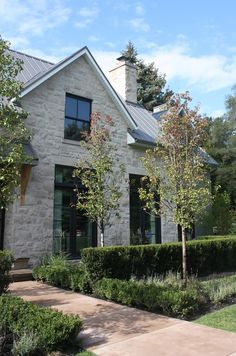 Love the gray stone exterior, black tdl windows and metal roof -- farmhouse meets industrial