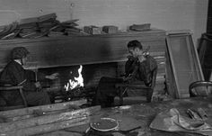 Warsaw insurgents Jerzy Sikorski and Wieslaw Chzhanovsky warm themselves by the fireplace after the uprising has been defeated. They both wear Waffen SS tunics and carry German MP-40 sub machine guns; the fighter on left is wearing a Waffen SS helmet. Oct 4, 1944.