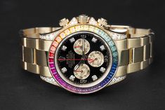 The Rolex Daytona (Ref. 116595RBOW) shines bright with its beautiful yellow gold case and all its colourful gemstones set on the bezel. The watch is without any doubt an absolute eye-catcher and is guaranteed to attract a lot of attention. Buy Rolex, Rolex Models, Luxury Watch Brands, Sapphire Bracelet, Rolex Daytona, Gemstone Colors, Catcher, Rolex Watches, Bright