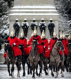 The Life Guards of the HCMR pass the Guards Memorial as they arrive on Horse Guards Parade for the daily Queen's Life Guard.