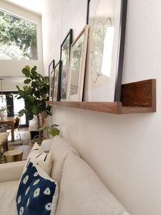 Dec 2019 - In this post Im sharing ten easy steps for you can use to make your very own 10 foot long picture ledge; for under 50 bucks! Picture Wall Living Room, Family Room Walls, Living Room Pictures, Picture Shelves, Picture Ledge, Photo Shelf, Apartment Makeover, Apartment 9, Decorating Small Spaces
