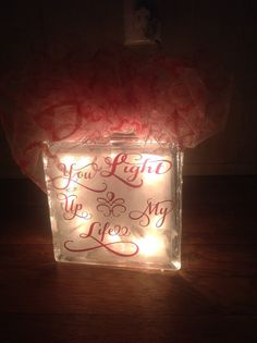 Glass Block lit up that says You Light Up My Life in Red Lettering with White Tulle bow on top with red glitter hearts on the tulle. Made in