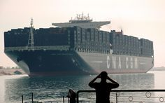 An Egyptian man watches the largest and the newest container ship in the world, the British-flagged CMA CGM Marco Polo, sail through the Suez Canal as it passes the port of Ismailia. The South Korean built ship can carry some 16,000 containers or 167,000 tons