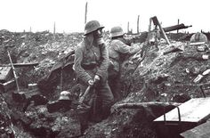 German troops in the trenches near Verdun. The soldier nearest the camera prepares to throw a grenade. To his left, a machine gunner scans no man's land for targets.
