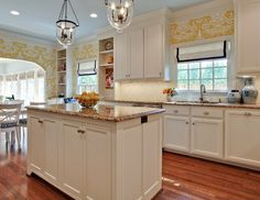 Beautiful kitchen with creamy white shaker cabinets paired with brown granite countertops and white porcelain diamond pattern tile backsplash.