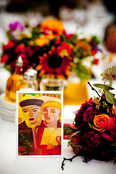 reception table setting with orange, dark pink, dark purple, and green floral arrangements and colorful artwork on a card indicating table assignments - photo by New Mexico based wedding photographers Twin Lens