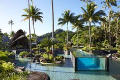 """Laucala Resort Fidji Planté au beau milieu des îles Fidji, Laucala Island est un petit éden préservé, enfoui dans la végétation tropicale et accessible uniquement sur invitation. Outre ses 25 villas privées, l'hôtel excite les happy few avec sa """"piscine dans la piscine"""" hors norme. Un long couloir de verre transparent posé sur un bassin lagon, contemplant l'océan. De quoi donner l'envie immédiate d'y plonger."""