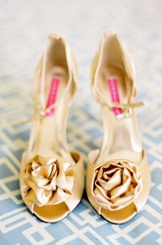 Gold wedding shoes embellished with a fabric rose are a glamorous addition to a sustainable, chic wedding.
