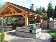 HGTV Gardens is showing you a covered outdoor kitchen with a bar.