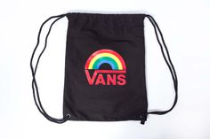 Mochila saco Vans de color negro, con el logo del arcoiris de la línea Rainbow estampado en el centro. Cordones negros, fabricada 100% en algodón.