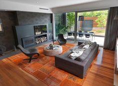 Wohnzimmer mit schwarzem Kamin und Kilim mit exotischen Mustern