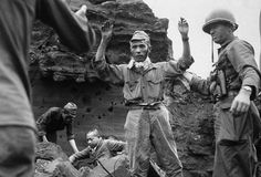 With his hands in the air, the first of 20 Japanese emerges from a cave on Iwo Jima, on April 5, 1945. The group had been hiding for several days.	 (AP Photo/U.S. Army Signal Corps)
