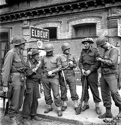 Normandy (Misc.) - Canadians meet Americans: Pte. W.R.Burns and Sgt. K.C. Lingen of the Royal Hamilton Light Infantry talk with Cpl. J.E. Junus, Capt. A.A. Smith, Lt. Clair Jones, 1st Sgt. L.R. Huntingdon, members of 2nd U.S. Armored Division. August 27, 1944, Elbeuf, France.