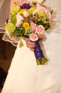 bridal bouquet with pink peonies, purple  lisianthus, pink spray roses, purple carnations, green  viburnum, yellow daffodils, wax flower, and queen Anne's lace.  Flowers by Bloom and Leaf Event Florist.  Photo by Tim Malkemus Photography.