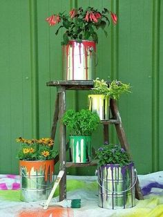 The paint cans as flower containers is perfect for the little ladder that displays them. Love this idea.