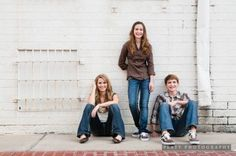 I like the idea of having the youngest 1 stand & the two older siblings sit against a wall.