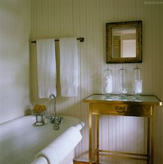 The simple bathroom has a clapboard wall and a brass table with a glass top ~ Nanette Brown in the Hamptons