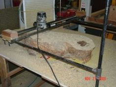 Router Planing Sled - Homemade router planing sled constructed from pipe, wood blocks, T-fittings, flanges, and angle iron.