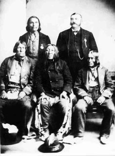 """Image of four Aboriginal male chiefs and an non-Aboriginal man posing for the camera; [indoor scene]. Note with photo: """"Cree Chiefs from Crooked Lake. Seated - Flying in a Circle, Big Child Star Blanket. Standing - O'Soup a Blackfoot, P. Hourie an interpreter. Taken at Brantford, Ontario, at unveiling of Brant memorial Oct. 13, 1886. O'Soup Chippewa Chief / P. Hourie Interpreter / Front: Flying in a Circle / Big Child Mistawasis / Star Blanket Ahtahkakoop / names according to two of Rev…"""
