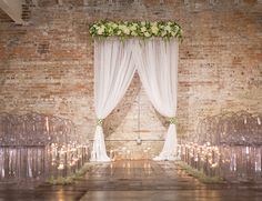green and white florals + wedding ceremony altar // white curtains, ghost chairs, candles, brick loft