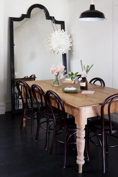 Chic dining room with black arched floor mirror at the end of the space reflecting the black enamel pendant hung over a rustic farmhouse dining table lined with Thonet Bentwood chairs atop black hardwood floors. Table And Chairs, Dining Chairs, Room Chairs, Antique Dining Tables, Table Legs, Office Chairs, Dining Set, Bentwood Chairs, Metal Chairs