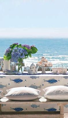 Coastal dining space set with a view and spring flowers