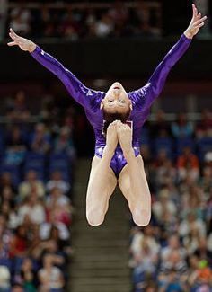 Head over heels, Kyla Ross performs on the balance beam.