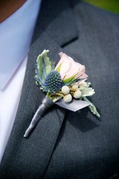 Textural boutonniere featuring blush spray rose, blue thistle, brunnia berries, and dusty miller. Floral design by Modern Day Events + Floral. Photography by Jen Kroll Photography.