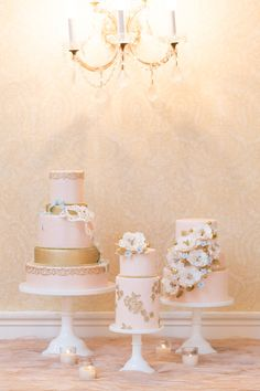Multiple cakes, white and gold, coordinating but not matching