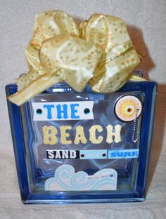 This is a beautiful Glass Block 8x8x3 featuring THE BEACH sand and surf in 3D stickers with a Yellow/Gold mesh ribbon. The price shown is for the block as it is shown here, however, we can customize a