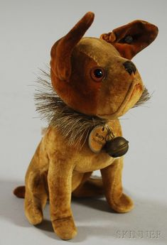 """Early Steiff Golden Brown Velvet """"Bully"""" Dog, Germany, jointed neck, brown glass eyes, embroidered nose, mouth formed by piped fabric, underscored STEIFF button in ear, defined haunches, bristle ruff around neck, with bell and paper tag BULLY Steiff-Original, seated ht. to tip of ear 6 1/4 in."""