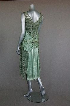 A Jeanne Paquin labelled green lace and satin dress, Summer 1927 Large woven satin label, dated and numbered 40563, with diagonal satin bands converging at the front with two floating panels, interal satin waist slip, bust 92cm, 36in - Estimate £500 - £700 Condition: satin panel to front right side is splitting, slight soiling to satin piping on inside edge of neck opening, a few small breaks in the lace here and there but top of the inside petticoat has perished at the upper edge a...