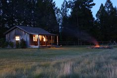 This Montana tiny home had natural wood siding, a shallow gable roof, front porch, fire-pit and rolling fields.