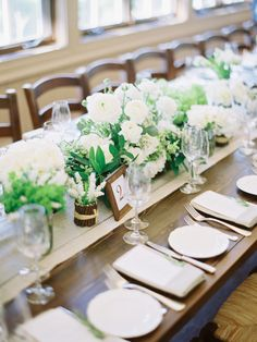 Linen table runners with low rows of green & white blooms - simple elegance. See more on http://www.StyleMePretty.com/2014/03/31/celebrity-stylists-wedding-at-bedford-post-inn/ Photography: Trent & Dara Of Trent Bailey Photography - www.trentbailey.com on #SMP