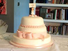 Torta comunione a tre piani decorata con la pasta di zucchero bianco  e rosa. La torta è pan di Spagna con la crema pasticcera e fragoline di bosco.