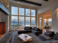 Okanagan Lakeview Home....Although I love many styles of homes, I don't usually go for the contemporary look. I do like this room though with the fireplace, the great view, the rug, and those sectionals. I love sectional sofas, they are so comfortable and inviting.