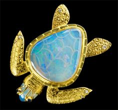 Turtle Enhancer    Brazilian crystal opal: 43.0 carats total weight (shell 36.2 carats).  Sapphires: .10 carats tcw. Michael & Judy Wallace (Wallace Goldsmithing):  Diamonds:  .19 carats tcw  Set in 18k yellow and green and 24k gold: total gold weight 36.2 grams.