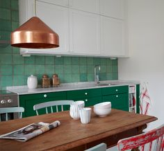 This green kitchen has an earthier feel thanks to tiles hand-crafted in Italy, a copper pendant, rustic wooden table, and a collection of vintage chairs. Copper Kitchen, Green Kitchen, Kitchen Tiles, Kitchen Colors, Kitchen Flooring, Earthy Kitchen, Copper Interior, Kitchen Interior, Kitchen Decor