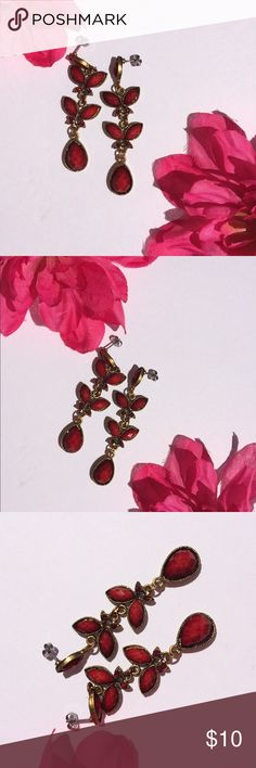 Red and gold dangling tear drop earrings Red and gold dangling tear drop earrings. Has a red bead type of jewel shaped like tear drops throughout. There are several small red diamonds as well. The red color is a deeper dark red around the edges. Has a dark brassy gold metal. The red beads/jewels do not fully fill in their metal spaces as seen in pictures but is not noticeable when wearing if at all. Jewelry Earrings