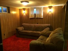 Before photo of our ugly  70's basement. Our older sofas need help also! We hate the ugly light sconces on the wall. Orange glass and black iron porch light on a wall. Yuck! The red and orange shag carpet is ugly but I cleaned it and it looks brand new.  The old women who lived in this house before us never went down in the basement.