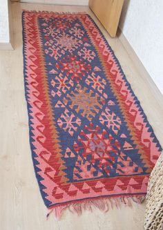 Long hand-loomed Turkish flat woven kilim. Kilim is a turkish word referring to flat woven rugs - rugs that have no pile. Traditionally kilims have a more geometric or angular design than hand knotted rugs. These vintage rugs were made with natural and vegetable dyes, due to vintage nature, you can see some variations in color throughout. This kilim would be a perfect pop of color in any narrow hallway or galley kitchen. Size —78 x 27 (92 x 31) Pattern — Small and geometric shapes, on bright…
