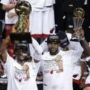Miami Heat's Dwyane Wade holds the Larry O'Brien NBA Championship Trophy, left, and LeBron James holds the Bill Russell NBA Finals Most Valuable Player Award after Game 7 of the NBA basketball championships, Friday, June 21, 2013, in Miami. The Miami Heat defeated the San Antonio Spurs 95-88 to win their second straight NBA championship. (AP Photo/Wilfredo Lee)