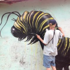 Street artist ROA (from Ghent, Belgium) at work on his yellow caterpillar in Gambia. A lovely coloured piece, as he usually works with only black and white. Roa is still on the graffiti circuit, but is also producing works for gallery shows on scrap metal and found wood. (photo © Roa)