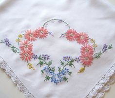 This is a very pretty table cloth, probably dating from the 1940s-1950s, made of a cotton mix with a sweet cotton lace edging. It has been expertly hand embroidered in each corner with flowers in lovely bright colours and is in very good condition. The tablecloth measures 37 x 33.5 (94cm x 85cm) and would add colour and gaiety to any tea table.    Please note that I will always refund any excess postage costs paid by buyers (less a sum for packaging) if costs turn out to be less than my…