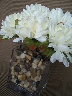Fake flowers in a vase with rocks as a center piece