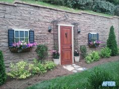 Clever idea to disguise a blah retaining wall! She used a 3.95-dollar reject door from Lowes and some misc scrap wood! Lovely!