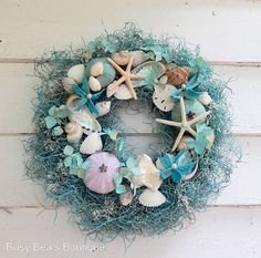 Teal blue natural grasses, white babys breath and blue-green glazed Spanish moss surround this nautical wreath brimming with starfish, sea urchins, white pencil starfish, sand dollars and an array of interesting shells. This would make a great centerpiece or that special touch for your beach house. The wreath base is handcrafted from twisted wisteria vines and wreaths are shipped in custom boxes for safe delivery and future storage. The featured wreath measures 13 inches across - but you can…